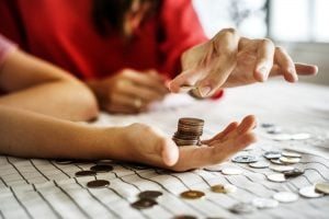 A person placing coins in another person's hand, seemingly counting them