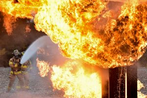 Fireman extinguishing a large fire - it can be caused by common packing mistakes