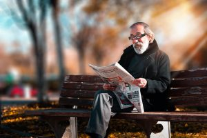 A gentleman in a park, reading newspaper