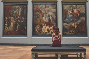 A girl sitting in front of three renaissance pictures in a gallery.