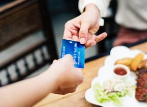 An individual paying for a nutritious meal via pay card