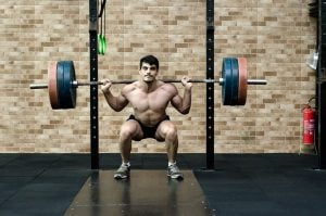 A man doing a squat with a heavy load.
