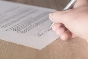 Person signing a contract.