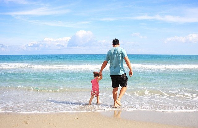 Father and daughter enjoying beach.