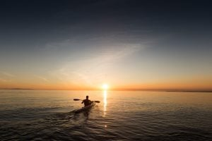 Picture of man kayaking into the sunset
