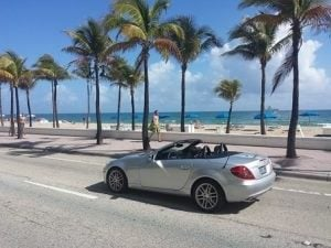 Cabriolet next to a beach and palm trees