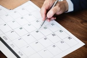 Person pointing at a calendar.