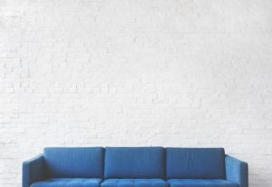Blue couch in front of a white brick wall
