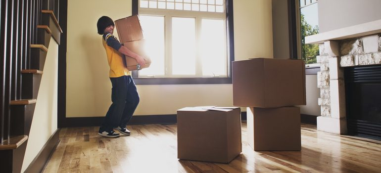 Boy carrying boxes in house