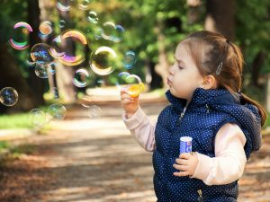 a young girl blowing soap bubbles