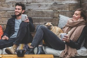 Man and woman with a pug drinking coffee