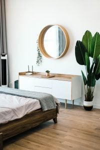 a bedroom with a plant, bed and a mirror on the wall
