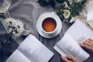A view of a cup of coffee and two books on a table.
