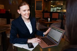 A woman smiling and holding a laptop.