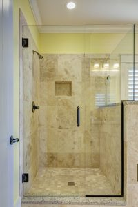 A shower with beige tiles.