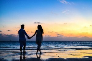 Couple holding hands and walking on seashore