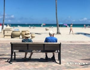 senior couple sitting on a bench near the beach