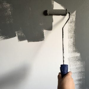 person painting a grey wall