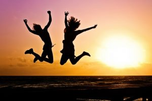 Two girls jumping on the beach