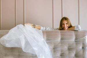 woman smiling behind a wrapped-up headboard
