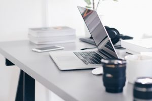 a laptop and a cup on a working desk