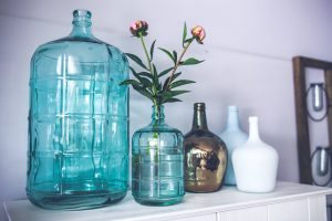 handle sentimental clutter by reusing it in your daily life. five vases on a shelf and one contains flowers