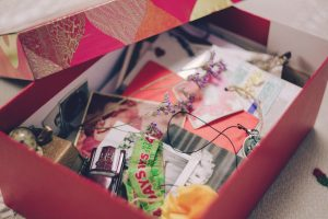 a box of sentimental clutter, cards, necklaces, bags, etc.