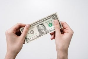 a dollar bill in a person`s hands