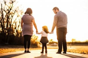 parents walking, holding their child`s arm during the day