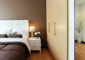 white bed next to a wardrobe in the bedroom