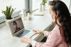 woman wearing mask and having a video call
