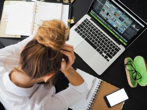 use moving insurance in order to avoid stress. a woman holding her head above a desk with a laptop, notebook and a phone