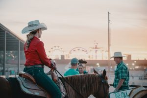 woman with a cowboy hat riding a horse