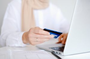 a woman with a scarf wearing a white shirt, is holding a credit card and looking at a grey laptop