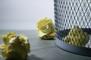 Protect your personal information by destroying all the old documents. A crumpled yellow paper inside and outside the garbage bin, a close-up photo of the bin