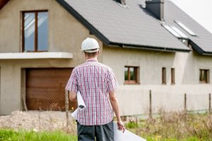 Picture of a contractor in front of the house. Make repairs before selling your luxury home.
