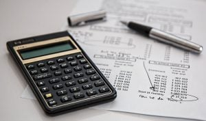 boost your relocation budget wisely. a calculator, a paper and a pen