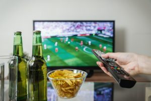 person watching a football match on tv with two beer bottles and a bowl of chips