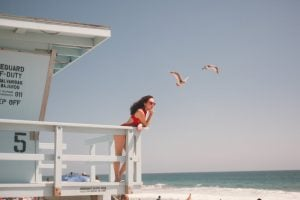 woman standing on a lifeguard post