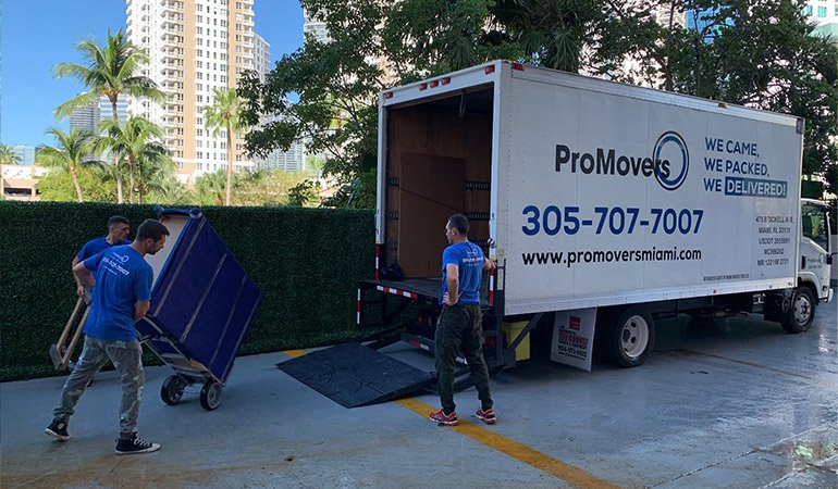 Movers ready to load, unload, and drive a truck.