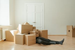 a person lying beyond several moving boxes before calling expert moving crews to help him