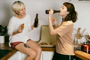 Picture of two girls eating pizza and drinking beer