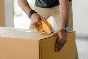 a person wearing a watch taping a moving box before the relocation