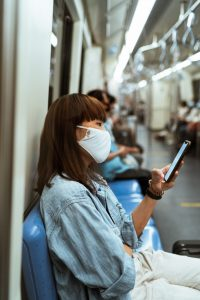 Picture of a woman on a train, wearing a mask. Having a home office means that you don't have to lose time and risk your health in public commute.