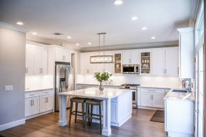 A kitchen with a dining space, chairs, cupboards, and kitchen appliances