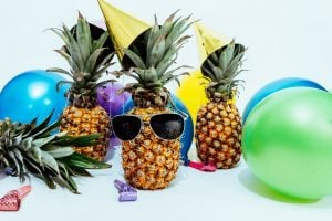 Pineapple with sunglasses and some balloons