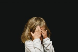 A distressed little girl covering her face with hands