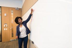 Woman writing on blackboard.