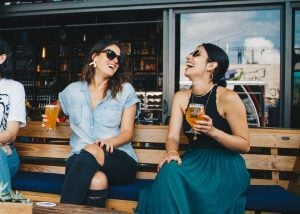 Two friends laughing over drinks.