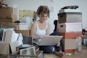 female typing on the laptop with cardboard boxes around